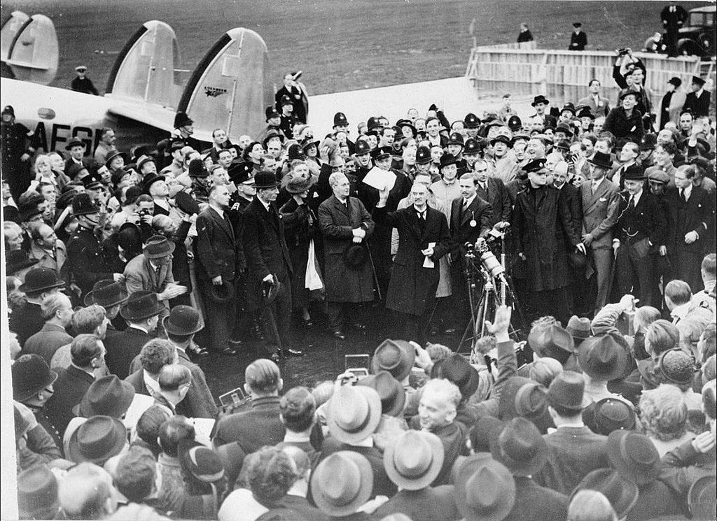 """二戰爆發前的1938年9月,英國首相張伯倫以出讓捷克斯洛伐克領土爲籌碼與納粹暴政極權談判苟合。這是9月30日他在返回的赫斯頓機場出示他與希特勒簽署的慕尼黑和平協議。他宣佈:通過與希特勒談判""""整個歐洲都可以找到和平""""。圖片來自維基百科"""