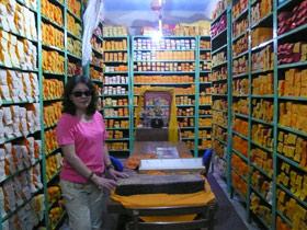 图片:本集受访人李江琳在达兰萨拉流亡政府所在地的藏经楼。架上所有经卷都是流亡藏民冒着生命危险携带到此的。(李江琳提供)