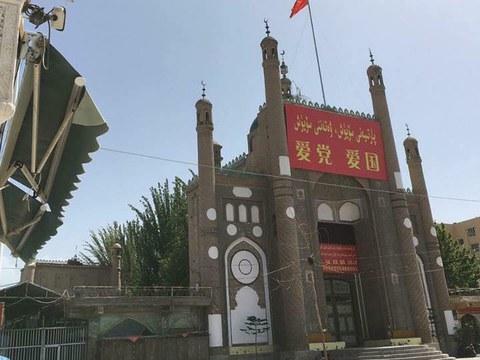 """新疆喀什地区叶城县加满清真寺悬挂中国国旗和宣传横幅,上面写着""""爱党,爱国家""""。"""