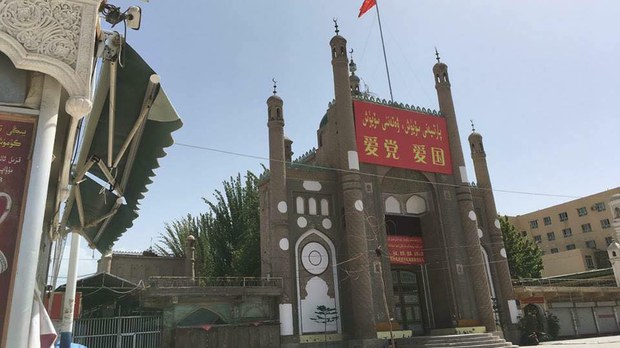 """新疆喀什地區葉城縣加滿清真寺懸掛中國國旗和宣傳橫幅,上面寫着""""愛黨,愛國家""""。"""