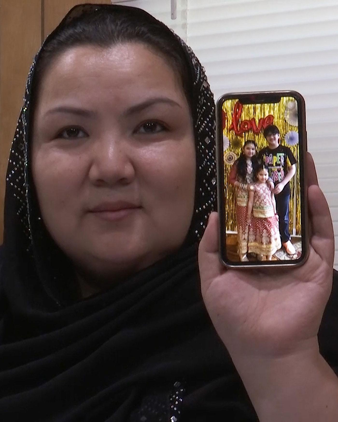 来自新疆的维吾尔人Zumret Dawut在美国弗吉尼亚的家里展示手机上她的孩子照片。(美联社)