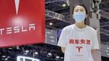 """2021年4月19日,上海車展,特斯拉維權女站在展車上,白色T恤上印有""""剎車失靈""""。"""