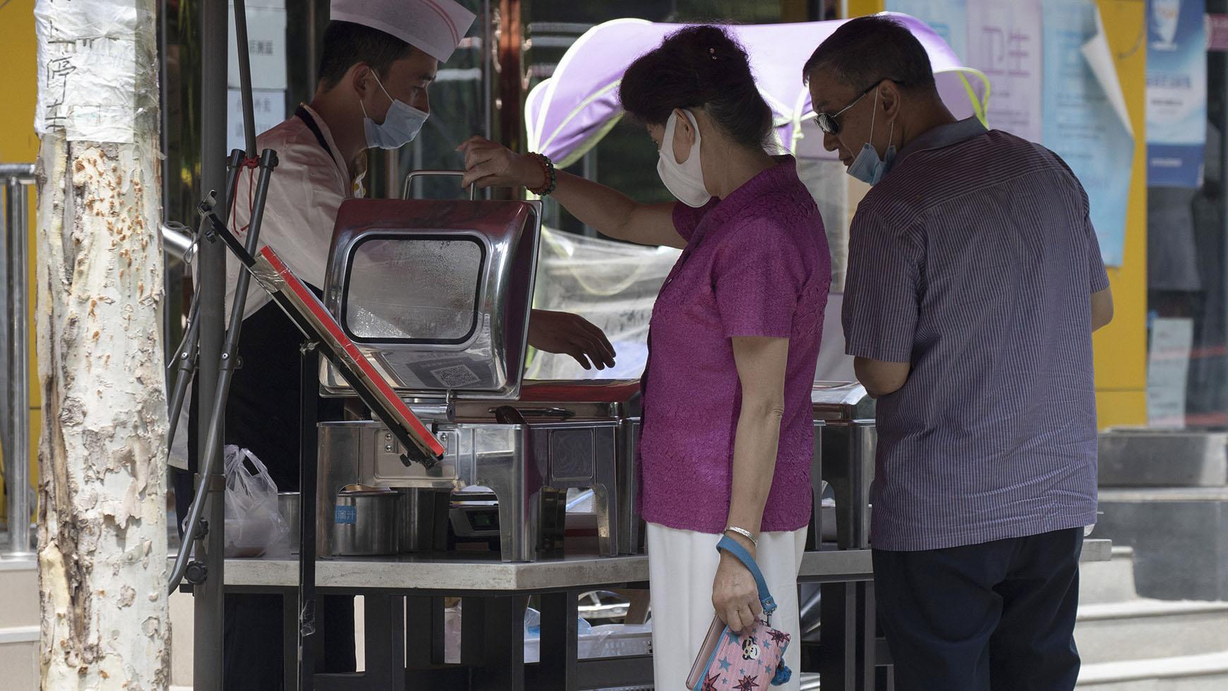中国经济复苏后又面临困难。图为2020年6月30日北京居民在路边购买食物。(美联社)