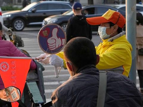 2021 年 10 月 20 日,交通督導員在北京的一個路口引導車流。