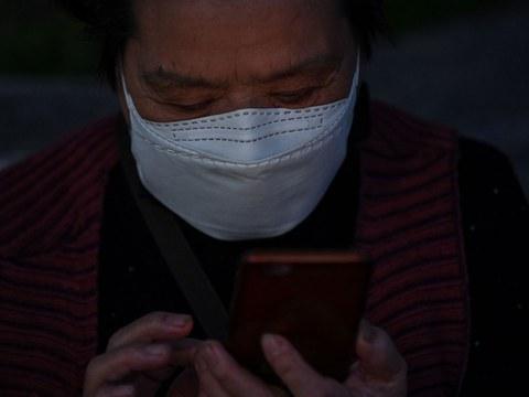 图为,一名戴着口罩的妇女在查看手机。