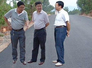 图片: 工作人员因觉原图背景不好,将照片合成成三位领导站在柏油马路上。 (网络图片/会理县政府网站)
