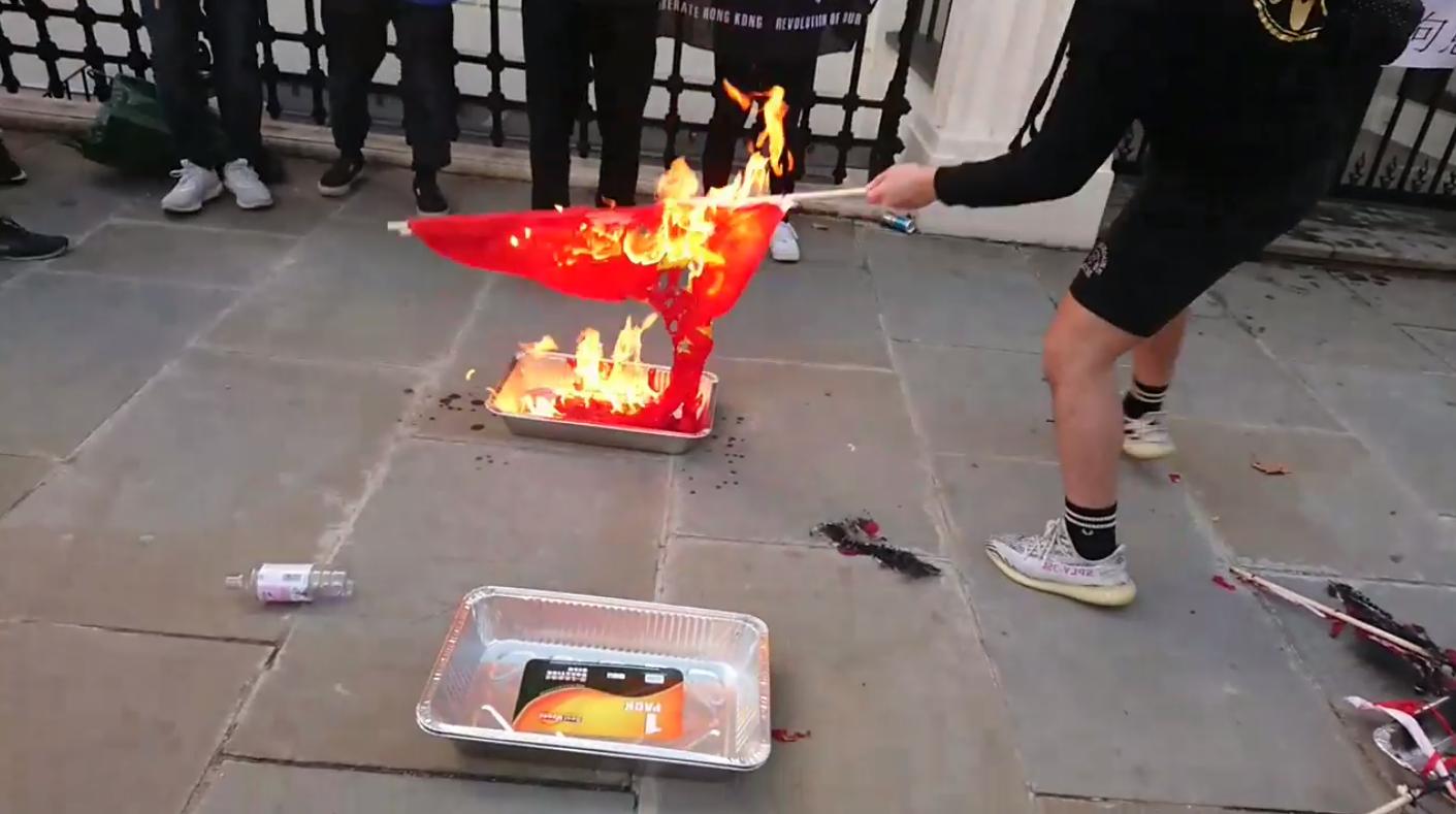 伦敦中国大使馆前民众在焚烧中国国旗。(维基百科)