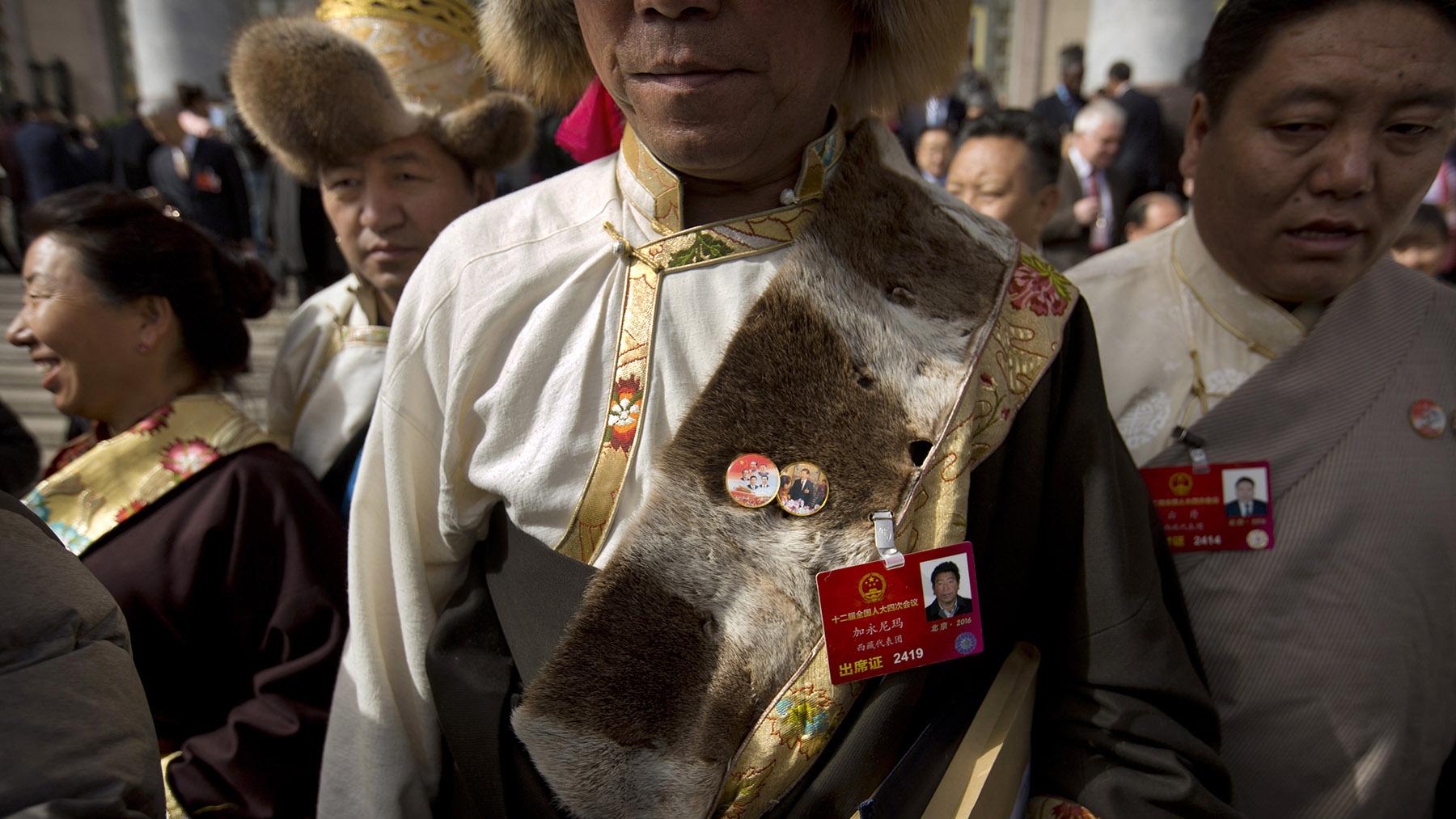 在北京出席会议的藏族代表戴着有习近平等国家领导人的胸章。(美联社资料图片)