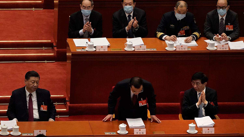 2021年3月5日,中国国务院总理李克强在人大会开幕式上致辞后鞠躬,左为习近平、右为王沪宁。(美联社)