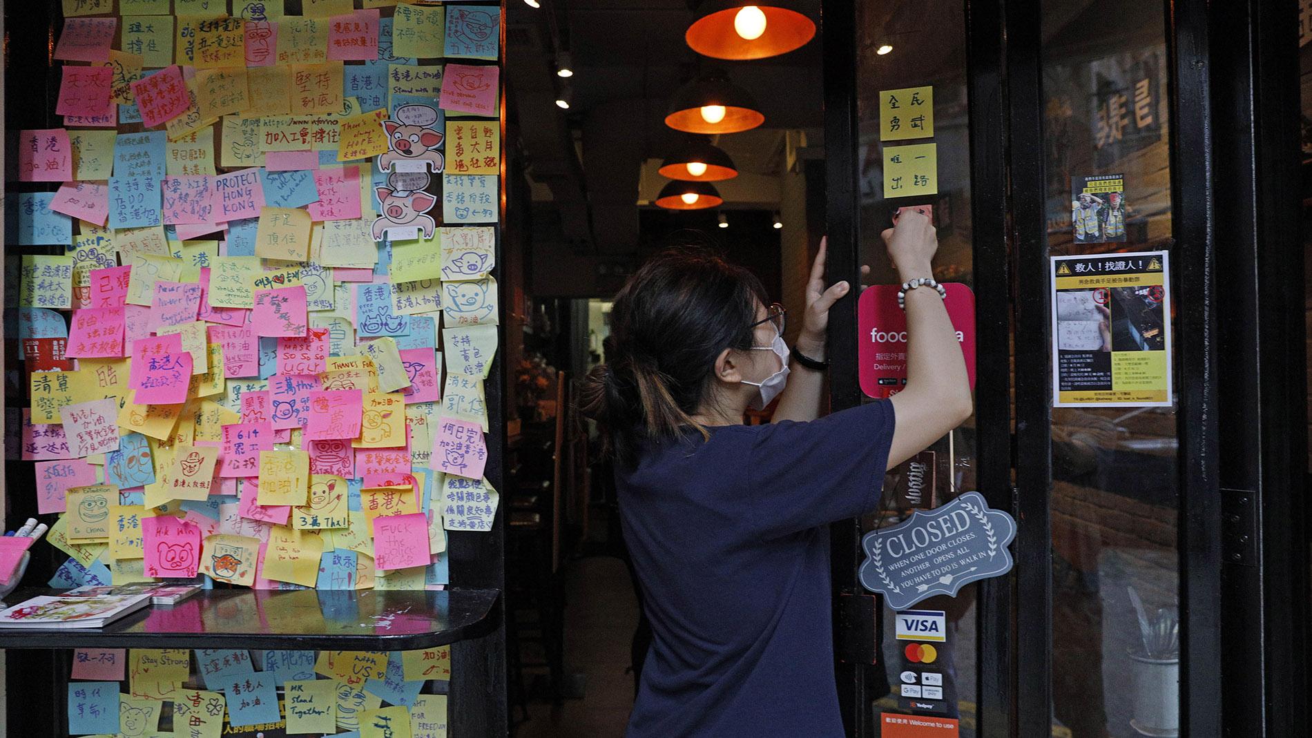 2020年7月2日,香港国安法通过之后,香港工人在清除街头的抗议标语。(美联社)