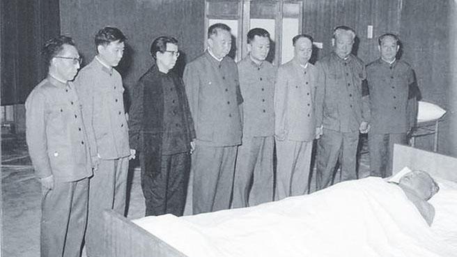 """1976年9月毛澤東去世當天,八大""""顧命大臣""""手挽手面對毛屍體的彩色照片,從左至右依次是:張春橋、王洪文、江青、華國鋒、毛遠新、姚文元、陳錫聯、汪東興。(Public Domain)"""