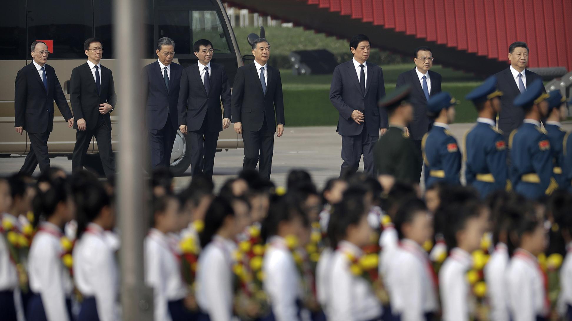 中国国家副主席王岐山(左一)和王沪宁(左四)等中共政治局常委。(美联社)