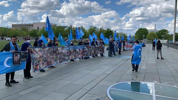 Gérmaniyediki Uyghurlar herqaysi sheherlerdin gérmaniye paytexti bérlin'gha kélip jem bolup, parlamént binasi aldida namayish qilmaqta. 2021-Yili 17-may.