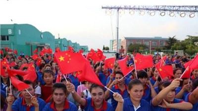 تەيگۇاڭ(Tai Guang) ئاياق زاۋۇتىدا قوللىرىدا خىتاي دۆلەت بايرىقىنى كۆتۈرۈۋالغان ئۇيغۇر ئىشلەمچىلەر. 2019-يىلى ئۆكتەبىر. (ASPI نىڭ دوكلاتىدىن ئېلىنغان)