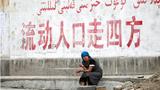 Bir Uyghur ayalning pilanliq tughur sho'ari astida olturghan körünüshi. 2009-Yili 14-iyul, ürümchi.