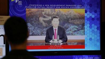 كىشىلەرنىڭ خىتاي رەئىسى شى جىنپىڭنىڭ APEC باش ئىجرائىيە ئەمەلدارى دىئالوگ يىغىنىدا سۆزلەۋاتقان ئېكرانغا قاراپ تۇرغان كۆرۈنۈش. 2020-يىلى 19-نويابىر.