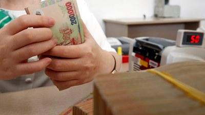 Một nhân viên ngân hàng ở Hà Nội đang đếm tiền đồng Việt Nam