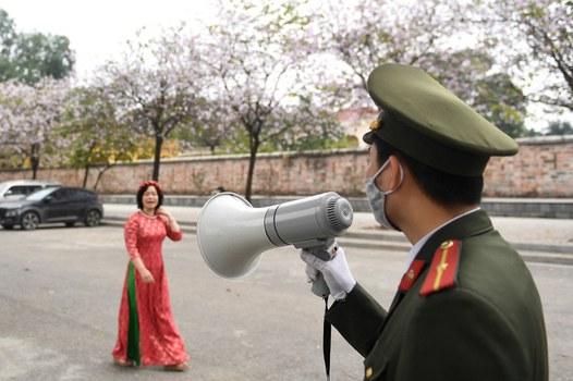 Cảnh sát cảnh báo người đi bộ đi gần khu vực cấm của chính phủ tại tòa nhà quốc hội ở Hà Nội vào ngày 3 tháng 3 năm 2021. AFP