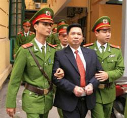 Công an dẫn giải TS Hà Vũ rời toà. AFP photo.