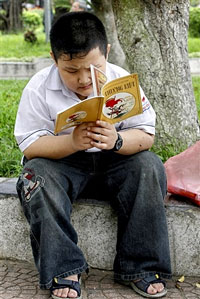 Cậu học sinh đọc sách tại công viên ở Hà Nội hôm 9-8-2007. AFP PHOTO