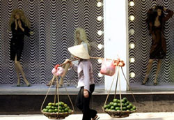 Người gánh hàng rong đi ngang qua một cửa tiệm sang trọng ở Hà Nội. AFP Photo.