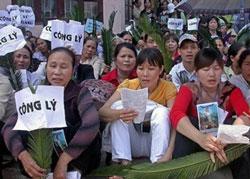 Các tín đồ Công giáo đang cầu nguyện bên ngoài tòa án Hà Nội xử những người bất đồng quan điểm về Tôn Giáo. AFP Photo/Ian Timberlake.