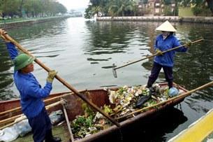 Công nhân vệ sinh hàng ngày phải vớt rác do người dân bỏ xuống hồ ở trung tâm Hà Nội.