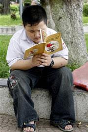 Cậu học sinh đọc sách tại công viên ở Hà Nội.(ảnh minh họa) AFP photo