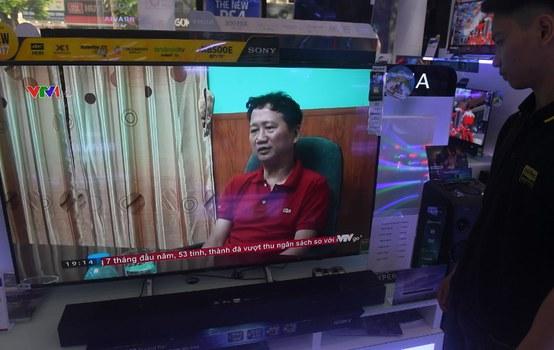 Một nhân viên bán hàng đang xem video ông Trịnh Xuân Thanh đầu thú trên kênh VTV1.