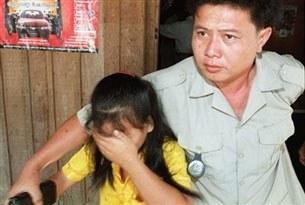 Cảnh sát Cambodia đưa bé gái Việt Nam, 11 tuổi, ra khỏi một nhà chứa mãi dâm ở Phnom Penh. AFP PHOTO