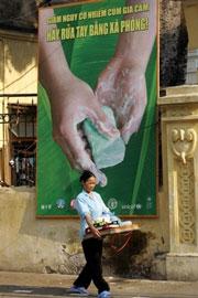 Đề phòng ngừa dịch bênh những bảng quảng cáo được dựng lên trên đường phố Hà Nội khuyến khích mọi người rửa tay trước khi ăn và nấu đồ dùng . AFP photo
