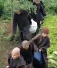 Các giáo thọ và tăng sinh phải di chuyển trong mưa dầm sau khi bị trục xuất khỏi tu viện. Hình trích từ video clip