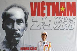 Một lính đứng gác trước biểu ngữ có ảnh Ô. Hồ Chí Minh. AFP