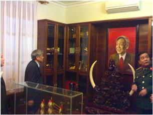 Chân dung bác Phiêu được đặt sau  một tác phẩm điêu khắc bằng gỗ quý có cẩn cặp ngà voi to tướng