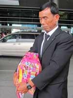 Cha của Hoàng Ngọc ôm chặt hài cốt con gái tại sân bay Tân Sơn Nhất. Photo courtesy of phapluat.com.vn