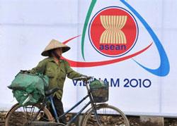 """Một người lượm ve chai đi ngang pano """"ASEAN - VIETNAM 2010"""" trên đường phố Hà Nội hôm 9/4/2010.AFP photo/Hoang Dinh Nam."""