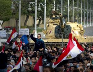 Lực lượng biểu tình tập trung trước 1 xe thiết giáp có trách nhiệm bảo vệ dinh tổng thống Ai Cập. AFP