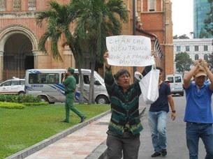 Ông Đinh Quang Tuyến trước Bưu điện TPHCM và bảng khẩu hiệu: Chần chừ kiện Trung Quốc ra tòa là phản bội dân tộc