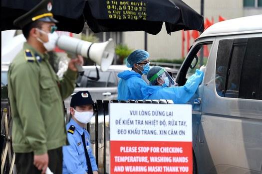 Hình minh hoạ. Nhân viên y tế kiểm tra thân nhiệt của khách đến bệnh viện Bạch Mai ở Hà Nội hôm 24/3/2020
