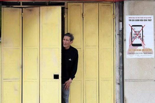 Hình minh hoạ. Một người đàn ông đứng trong nhà nhìn ra ngoài đường ở Hà Nội hôm 9/4/2020
