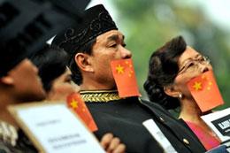 Người dân che miệng với lá cờ Trung Quốc trong một cuộc biểu tình trước tòa nhà diễn ra cuộc họp của Ủy ban Nhân quyền ASEAN (AICHR) ở Jakarta hôm 29/3/2010.AFP
