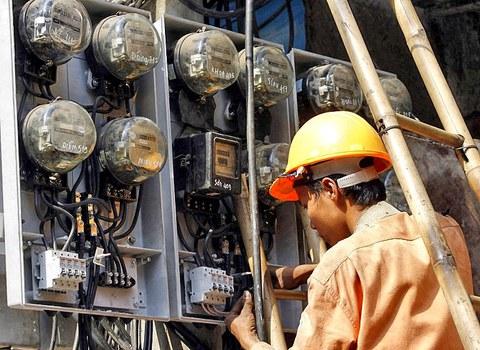 Công nhân Tập đoàn điện lực Việt Nam (EVN) đang kiểm tra đồng hồ điện