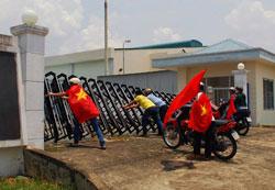 Những người biểu tình với cờ Việt Nam đang cố gắng phá cánh cổng một nhà máy ở Biên Hòa, tỉnh Đồng Nai hôm 14/5/2014. AFP photo