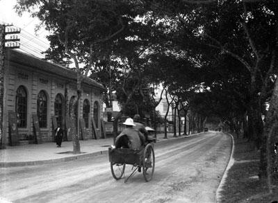 Một chiếc xe kéo chở khách trên một con đường ở Hải Phòng thời Pháp, khoảng năm 1900.