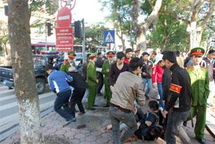 Công an, dân phòng vây bắt nhiều người, đưa lên xe chở đi.