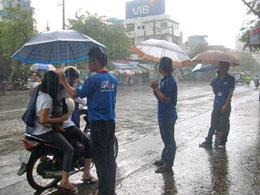 Hình ảnh đẹp trong mùa thi, các sinh viên che mưa cho thí sinh vào phòng thi tại TP.HCM. Ảnh Đặng Sinh/infonet