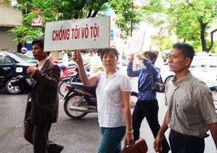 """LS Nguyễn Thị Dương Hà mang theo tấm biển """"Chồng Tôi Vô Tội"""""""
