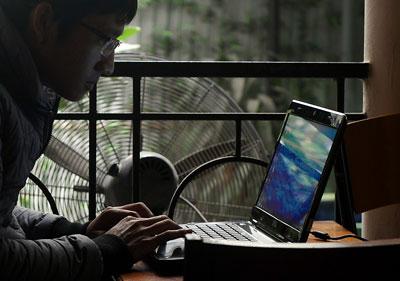 Một người dân sử dụng laptop lướt web trong một quán cà phê ở Hà Nội hôm 28/11/2013.