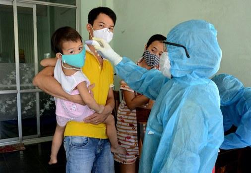 Hình minh hoạ. Một nhân viên y tế đang đo thân nhiệt cho cư dân tại khu vực phát hiện bệnh nhân nhiễm COVID-19 mới ở Đà Nẵng hôm 26/7/2020