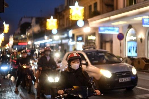 Người dân bật đèn chiếu sáng trên xe máy khi tham gia giao thông lúc trời tối tại Hà Nội.